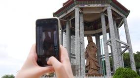 Frau, die Fotos durch Smartphone der Göttin der Statue der Gnade Guanyin oder Guan Yins im buddhistischen Tempel macht Besuchsang stock video footage