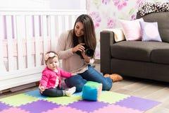 Frau, die Fotos eines Babys macht Stockfotografie