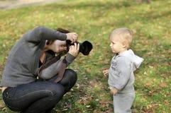 Frau, die Fotos eines kleinen Jungen macht Lizenzfreie Stockbilder