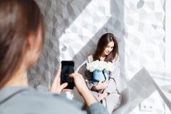 Frau, die Fotos ihrer Freundin mit Blumenblumenstrauß macht Lizenzfreie Stockfotos