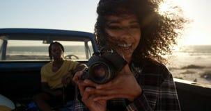 Frau, die Fotos mit Digitalkamera in einem Kleintransporter am Strand 4k macht stock footage