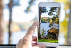 Frau, die Fotos mit einem Handy vom Fenster eines Autos macht Stockfotos