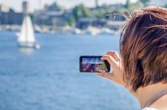 Frau, die Fotos mit ihrem Handy macht Stockbild