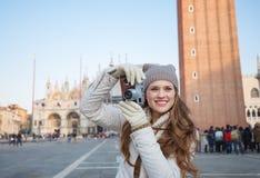 Frau, die Fotos mit Retro- Fotokamera auf Marktplatz San Marco macht Stockfoto