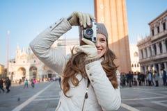 Frau, die Fotos mit Retro- Fotokamera auf Marktplatz San Marco macht Lizenzfreies Stockbild