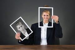 Frau, die Fotos mit verschiedenen Ausdrücken hält Stockfotografie