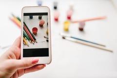 Frau, die Fotos mit Zellensmartphonekamera macht: Arbeitsplatz des Künstlers für das Zeichnen: farbige Bleistifte, Aquarell, Farb stockfotografie