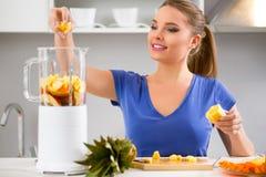 Frau, die Früchte Smoothies mit Juicermaschine macht Lizenzfreie Stockfotografie
