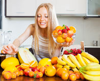 Frau, die Früchte von der Tabelle im Haus nimmt Stockfotografie