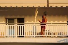 Frau, die früh auf dem Balkon morgens während der SUs steht Lizenzfreie Stockfotografie