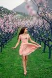 Frau, die Frühling auf dem grünen Gebiet mit blühenden Bäumen genießt Stockbilder