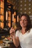 Frau, die an französischem Champagner nippt Stockbild