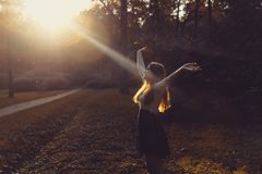 Frau, die frei auf Sonnenuntergang glaubt Schattenbild der ausgebreiteten Arme der Frau mit ihren Daumen oben, stehend im Wald im Stockfoto