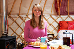 Frau, die Frühstück genießt, während, kampierend in traditionellem Yurt Stockfoto