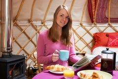 Frau, die Frühstück genießt, während, kampierend in traditionellem Yurt Stockfotos