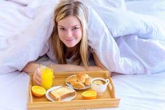 Frau, die Frühstück im Bett isst Glückliche Frau, die morgens Corn-Flakesgetreide im Bett genießt Stockbilder