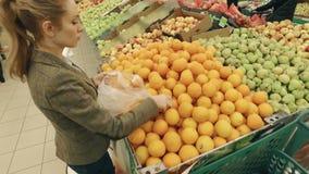 Frau, die frische Orange im modernen Supermarkt vorwählt stock video footage