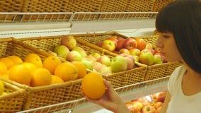 Frau, die frische Orangen in der Gemischtwarenladenerzeugnisabteilung vorwählt und sie riecht Junges hübsches Mädchen wählt Früch stock video