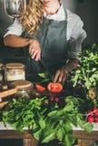 Frau, die frische reife Tomaten auf konkreter Küchenarbeitsplatte schneidet lizenzfreie stockfotografie