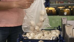 Frau, die frischen Pilz in der Gemischtwarenladenerzeugnisabteilung vorwählt stock footage