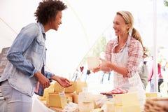Frau, die Frischkäse am Landwirt-Lebensmittel-Markt verkauft Stockfoto