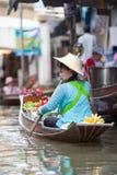 Frau, die fruirs an sich hin- und herbewegendem Markt verkauft Lizenzfreies Stockbild