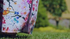 Frau, die Fußzehen auf grünes Gras im bunten Kleid gehen, Frühling, hat gekommenes im Freien stock footage