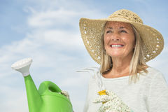 Frau, die Gartenarbeit-Ausrüstung gegen Himmel hält lizenzfreie stockbilder