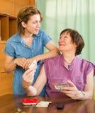 Frau, die gealterte Mutter um das Geld bittet Stockfotos