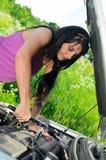 Frau, die gebrochenes Auto repariert Stockfotos