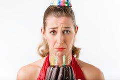 Frau, die Geburtstag mit den Kuchenkerzen abgewischt feiert Stockfoto