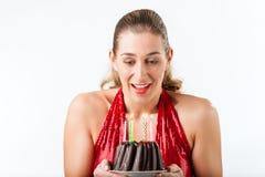Frau, die Geburtstag mit Kuchen und Kerzen feiert Lizenzfreies Stockfoto