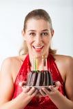 Frau, die Geburtstag mit Kuchen und Kerzen feiert stockfotos