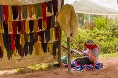 Frau, die gefärbte Wollgarne spinnt und trocknet Lizenzfreie Stockfotos