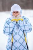 Frau, die gefrorene Hände mit Skipolen im Winter wärmt Stockbild