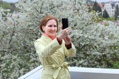 Frau, die gegen eine blühende Kirsche sich fotografiert Lizenzfreies Stockfoto