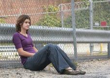 Frau, die gegen Zaun sitzt Lizenzfreies Stockfoto