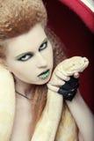 Frau, die gelbe Pythonschlange anhält lizenzfreie stockfotos