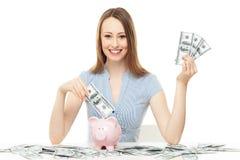 Frau, die Geld in piggy Querneigung einsetzt Lizenzfreie Stockfotografie