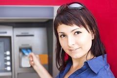 Frau, die Geld von der Kreditkarte an ATM zurücknimmt Lizenzfreie Stockfotos