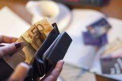 Frau, die Geldbörse und Geld halten und einige Kreditkarten auf dem tabl Lizenzfreie Stockbilder
