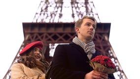 Frau, die geliebten Mann mit Blumenstrauß mit Verlegenheit, spät nach Datum betrachtet lizenzfreie stockfotografie
