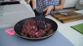 Frau, die Gemüse und Rindfleisch mit Tomaten brät stock footage