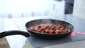 Frau, die Gemüse und Rindfleisch mit Tomaten brät stock video