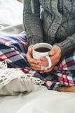 Frau, die gemütliche Pyjamas und trinkenden Tee der grauen Wolljacke auf einem Bett trägt Lizenzfreie Stockfotografie