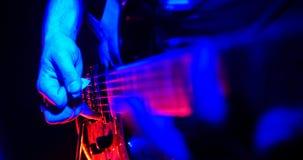 Frau, die Gesangschüssel und Gesang, in der purpurroten und blauen Beleuchtung spielt Gitarrist spielt die Gitarre Die Gitarre be lizenzfreie stockfotos