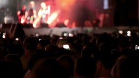 Frau, die Gesangschüssel und Gesang, in der purpurroten und blauen Beleuchtung spielt Obenliegende Menge stufe Helle Lichter stock footage