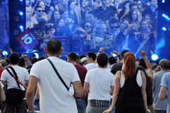 Frau, die Gesangschüssel und Gesang, in der purpurroten und blauen Beleuchtung spielt Stockfoto