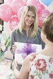 Frau, die Geschenk an der Babyparty empfängt Stockbilder