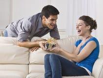 Frau, die am Geschenk lacht stockfoto